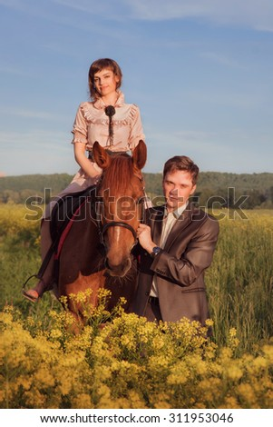 The man being led by the bridle the horse riding girl. Couple in love with a horse in a field with yellow flowers against the sky