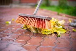 the man cleans the fallen leaves with a broom