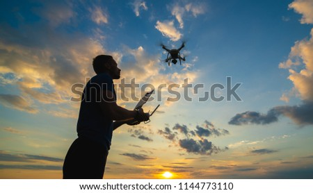 The man controls a quadrocopter on the sunrise background