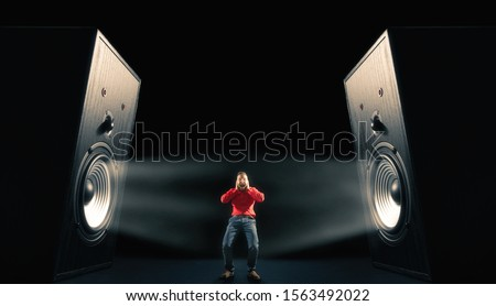 Photo of  The man cover his ears from loud noise wafting out from big sound speakers with funny faces. On black background. Image.