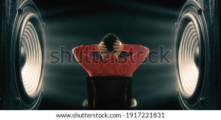 The man covers his ears from the powerful sound from the speakers. Photo stock ©