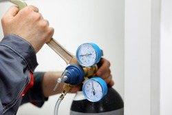the man disconnects the pressure gauge from the compressed gas cylinder. Testing the metrological pressure sensor.