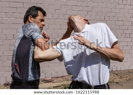 The man fixes the attacker`s elbow, while performing a brutal technique. Close up. Martial arts instructors demonstrate self-defense techniques of Krav Maga