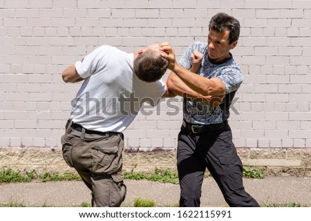 The man fixes the attacker`s elbow, while performing a brutal technique.  Half-lenght. Martial arts instructors demonstrate self-defense techniques of Krav Maga