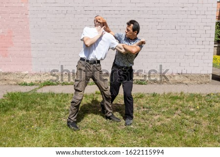 The man fixes the attacker`s elbow, while performing a brutal technique. Martial arts instructors demonstrate self-defense techniques of Krav Maga