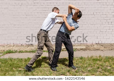 The man fixes the hands of the attacker, while performing an elbow strike in the jaw. Martial arts instructors demonstrate self-defense techniques of Krav Maga