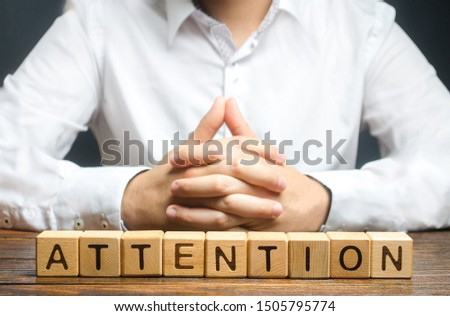 The man folded his hands in the lock and the word Attention. Focus on the point. Self-discipline and perseverance. Important message. In the spotlight. teacher, superior, businessman.