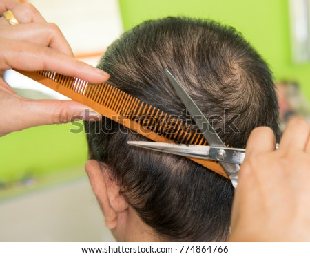 The man getting haircut from female hairdresser at salon, Barber using scissors and comb, Woman short hair cutting with scissors, selective focus,  #774864766