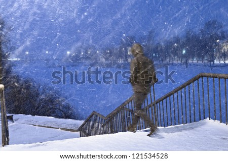 The man going down on steps from the bridge in a heavy snowfall.