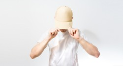 the man, guy in the blank white, beige baseball cap,  on a white background, mock up, free space, logo presentation , template for print,