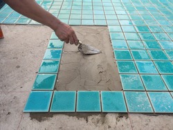 The man hand while using spacer for installing tiles. construction work.Construction Pool.