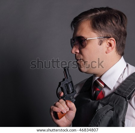 The man in a bullet-proof vest with a revolver on a grey background