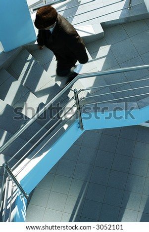 The man in a coat and a cap walking upstairs