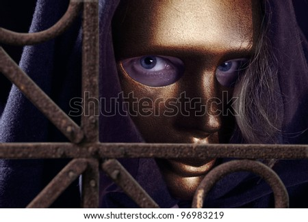 The man  in a gold mask behind a rusty fence