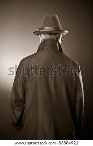 The man in a raincoat and a hat. The rear view