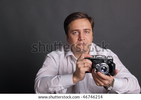 The man in a white shirt with the ancient camera on darkly grey background