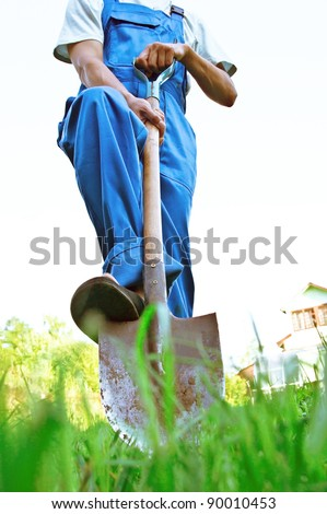 The man in dark blue overalls digs a shovel a ground