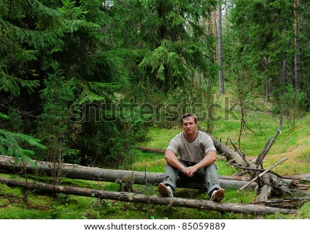 The man in  forest sits on a log