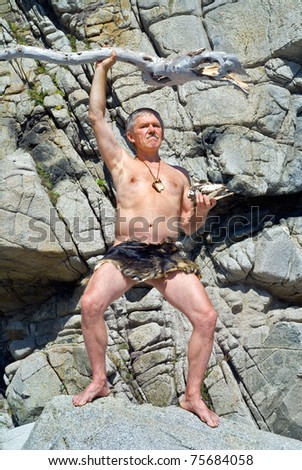 The man in loin-cloth stands at rocks with cudgel and skull in his hands. Stock photo ©