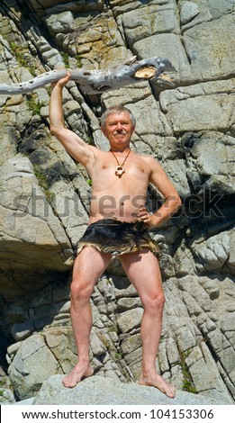 The man in loin-cloth stands at rocks with cudgel in his hands. Stock photo ©