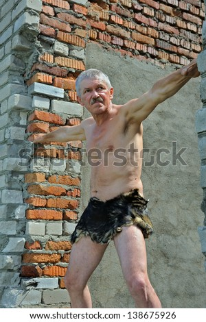 The man in loin-cloth stands at ruins of old building. Stock photo ©
