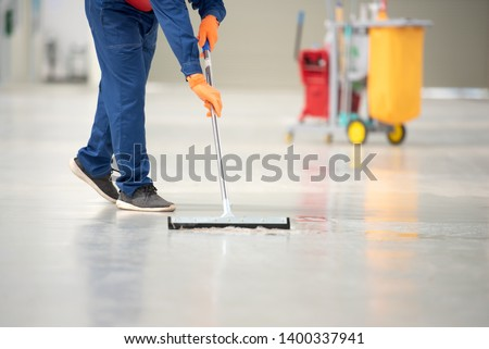 The man in the repairman is holding a mop in a white suit, cleaning the protective clothing of the new epoxy floor in an empty warehouse or car service center. #1400337941