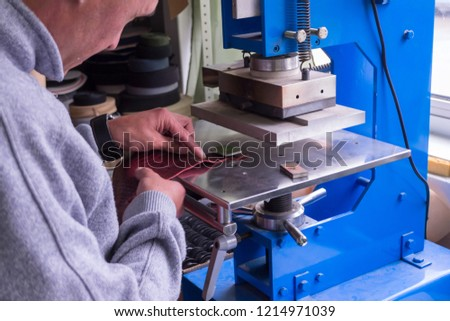 The man in the workshop presses the lever on the press machine to get the embossed logo and letters on the leather product that heats the cliche and squeezes the desired image on the material