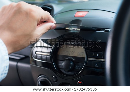 The man inserting CD to CD player in the car. Car audio system concept. Сток-фото ©