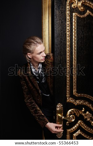 The man inserts a key into a keyhole of a black-gold door