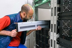 The man installs a new battery into the uninterruptible power supply. Replacing the power module in the server room rack. Maintenance of data center equipment.