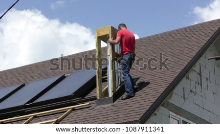 The man is building a chimney Construction and insulation of the roof chimney #1087911341