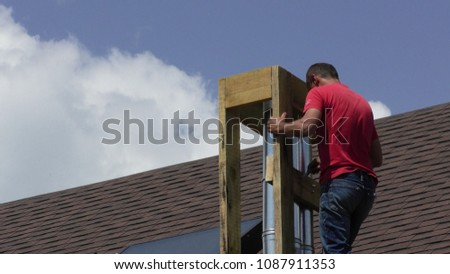 The man is building a chimney Construction and insulation of the roof chimney #1087911353