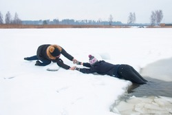 The man is drowning in icy water. One woman rescues Woman from icy water, Rescue man from water