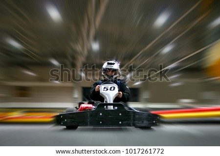 The man is going on the go-kart on karting track indoors. He is wearing a helmet.