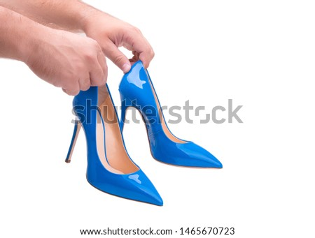 The man is holding high-heeled shoes. Blue high-heeled shoes. #1465670723