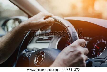 The man is holding his hands on the steering wheel of the car. The concept of driving a car. The interior of a modern car. View of the steering wheel, the dashboard of the car.