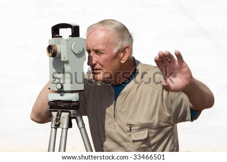 The man is looking through optical instrument