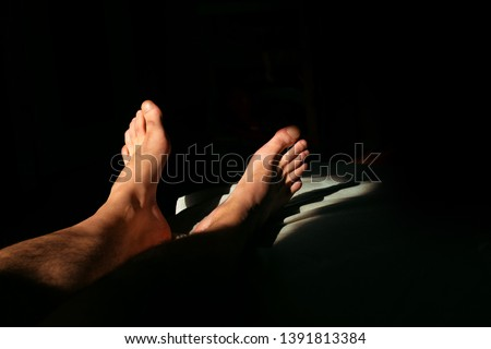 The man is lying on the bed and is resting.naked male legs in sunlight