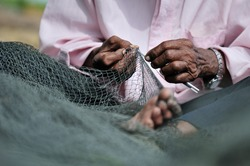 the man is mending nets fishing on the boat located at Marang Fishing village, a famous tourist destination in Terengganu, Malaysia ( selective focus)