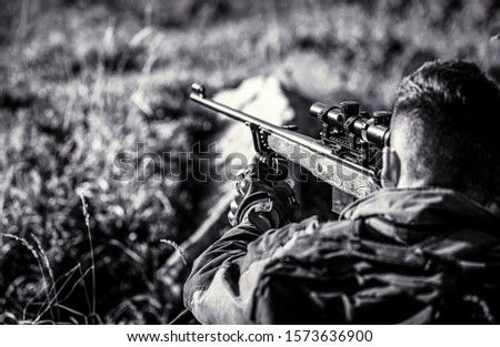 The man is on the hunt. Hunt hunting rifle. Hunter man. Hunting period. Male with a gun. Close up. Hunter with hunting gun and hunting form to hunt. Hunter is aiming. Black and white.