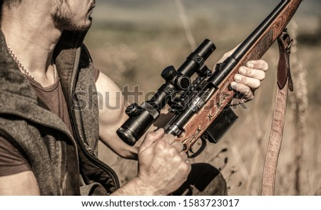 The man is on the hunt. Hunt hunting rifle. Hunter man. Hunting period. Male with a gun. Close up. Hunter with hunting gun and hunting form to hunt. Hunter is aiming. Shooter sighting in the target.