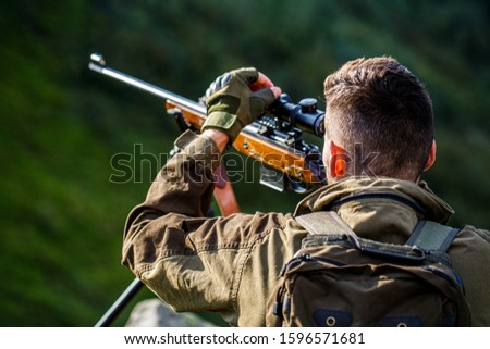 The man is on the hunt. Hunt hunting rifle. Hunter man. Shooter sighting in the target. Hunting period. Male with a gun. Close up. Hunter with hunting gun and hunting form to hunt. Hunter is aiming.