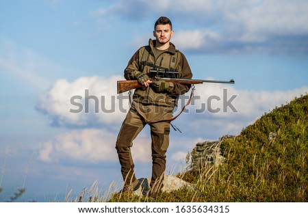 The man is on the hunt. Hunt hunting rifle. Hunter with hunting gun and hunting form to hunt sky background. Hunter is aiming. Hunter man. Shooter sighting in the target. Hunting period.
