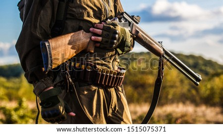 The man is on the hunt. Hunter man. Hunting period, autumn season. Male with a gun. Hunter with a backpack and a hunting gun. A hunter with a hunting gun and hunting form to hunt.