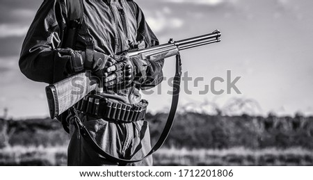 The man is on the hunt. Hunting period. Male with a gun. Hunter with a backpack and a hunting gun. A hunter with a hunting gun and hunting form to hunt. Hunter man. Black and white.