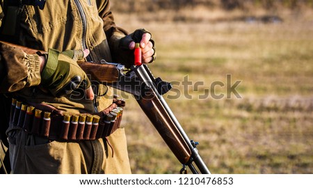 The man is on the hunt, sport. Hunter man. Hunting period. Male with a gun, rifle. Man is charging a hunting rifle. Process of hunting during hunting season. Male hunter in ready to hunt. Closeup.