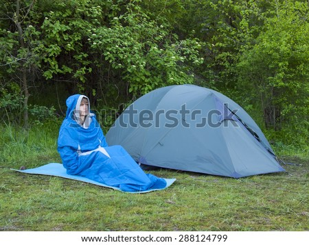 The man is resting in a sleeping bag on the background of tents and green forests.