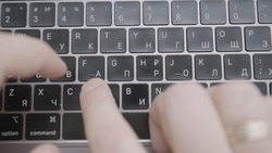 The man is texting quickly with his hands on a black keyboard with an English-Russian layout. Action. A man writes a letter or a message on on keyboard of a computer or laptop.
