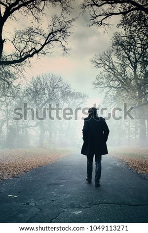 The man is walking along the road in the fog