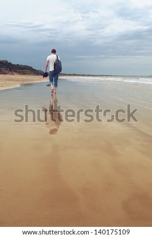 the man is walking on the beach